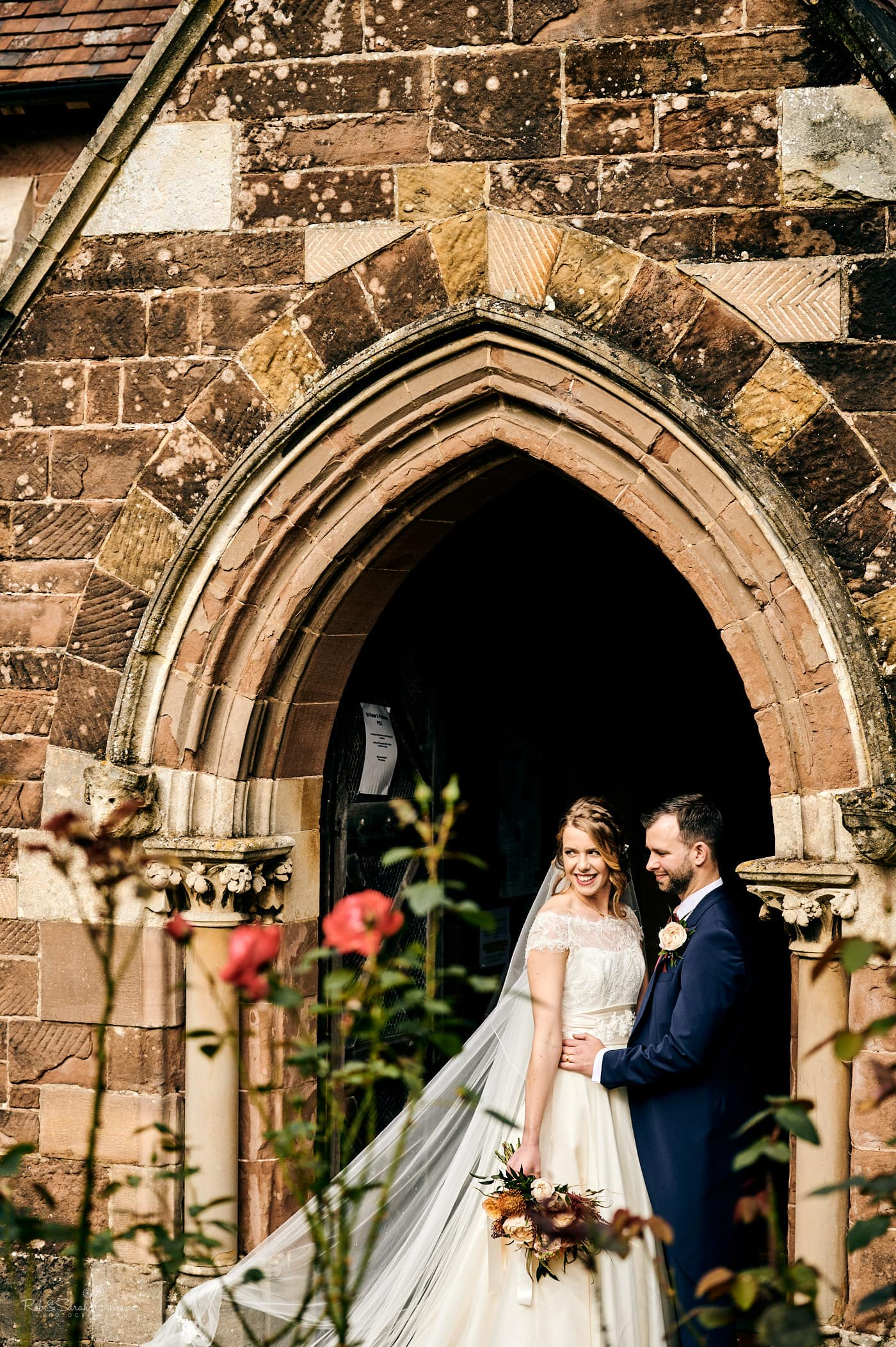 Bride and groom in archway at St Peter's church Pedmore