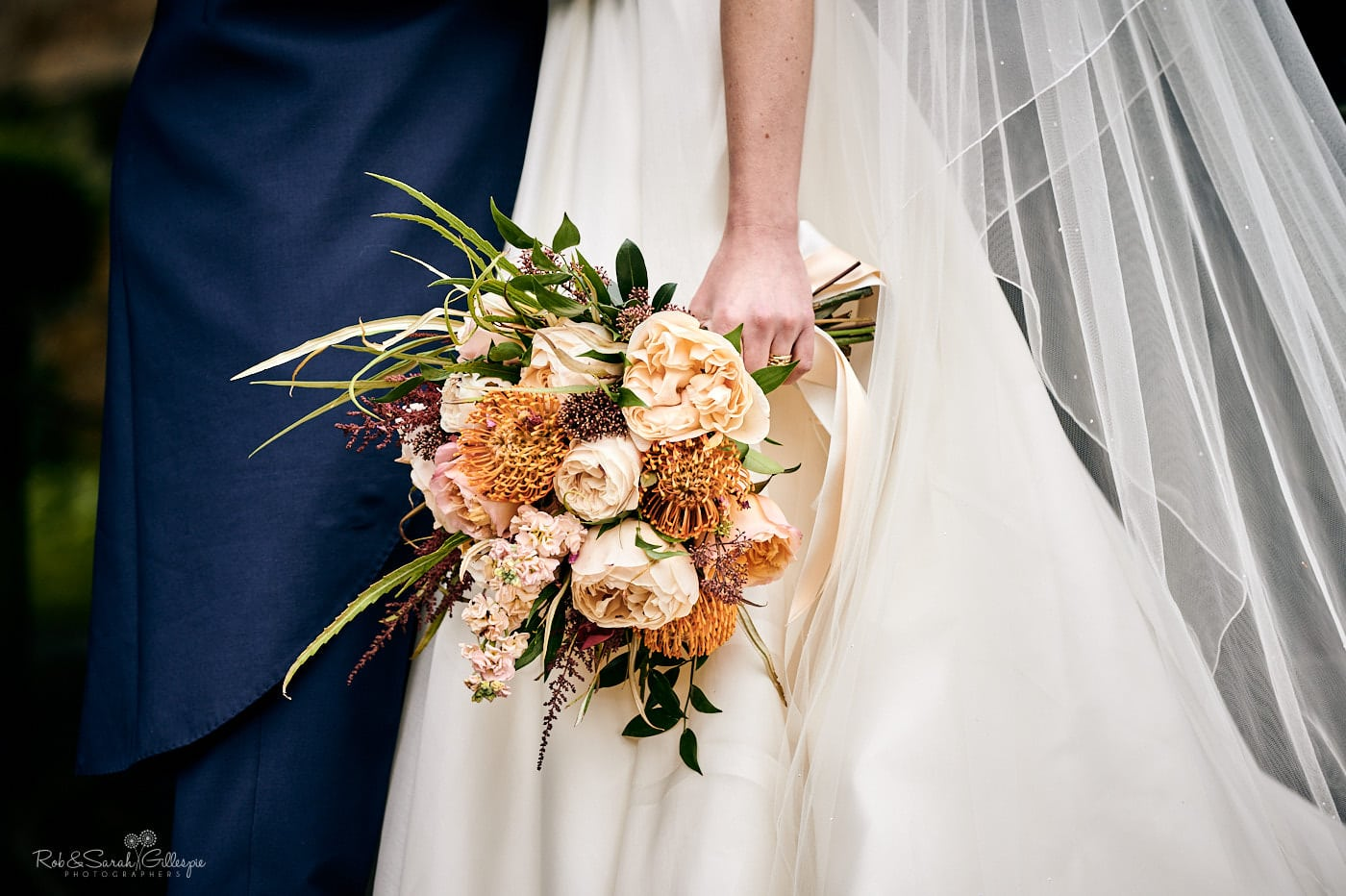 Close up of bride's bouquet and wedding dress