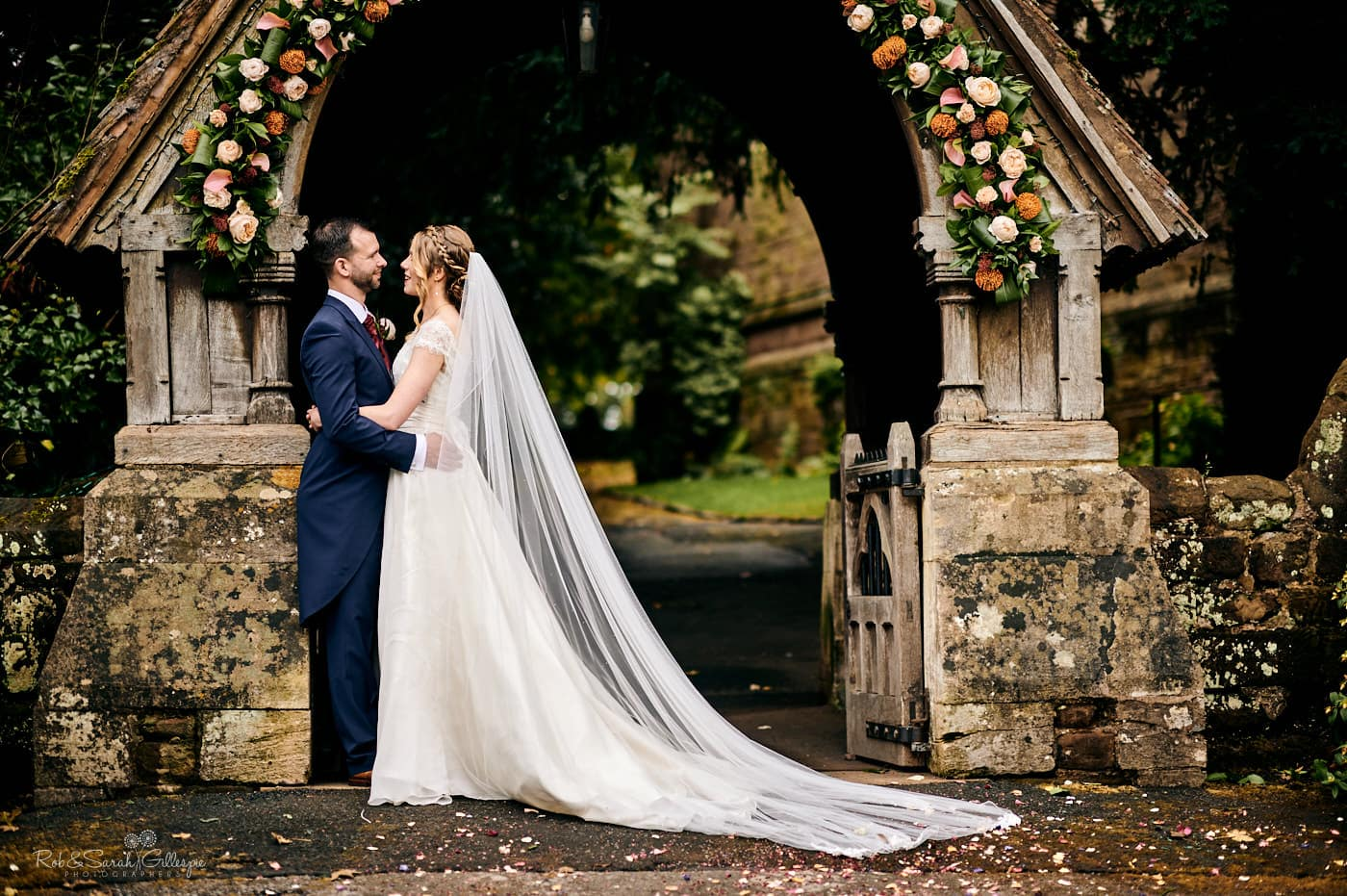 Bride and groom under lychgate at St Peter's church Pedmore