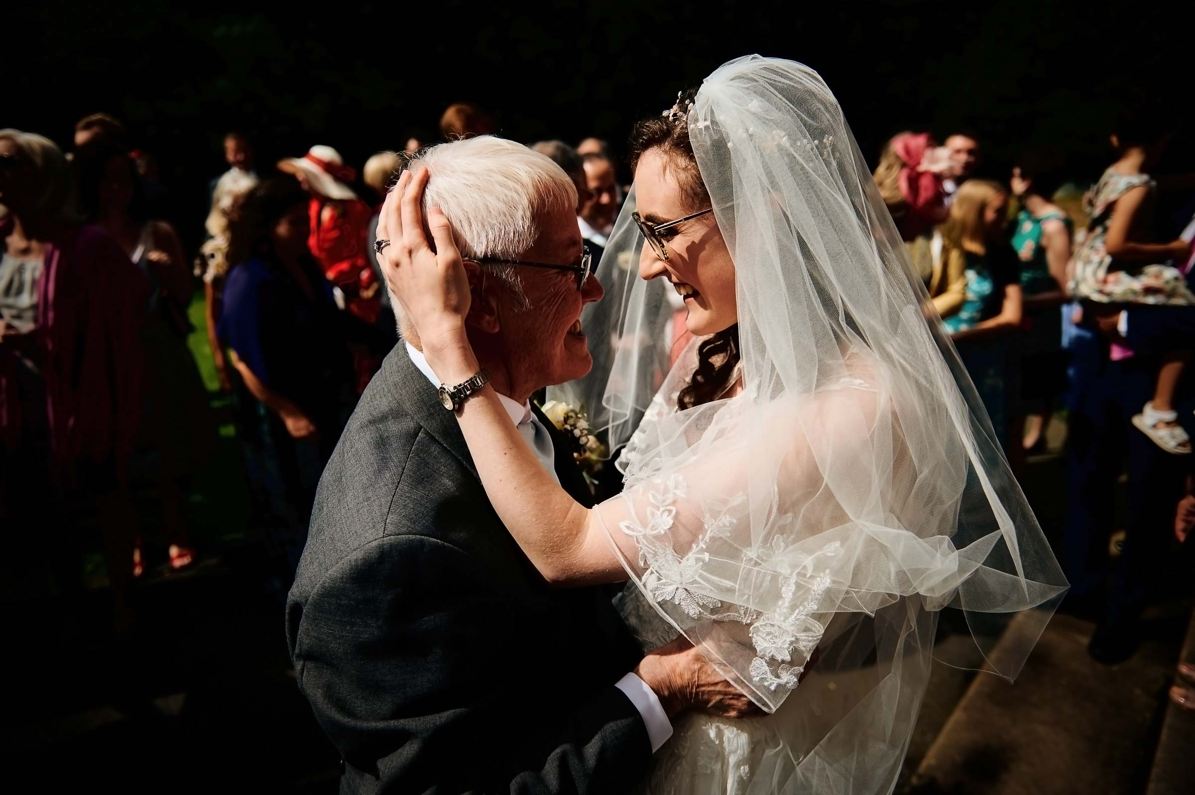 Bride hugs grandfather after wedding ceremony