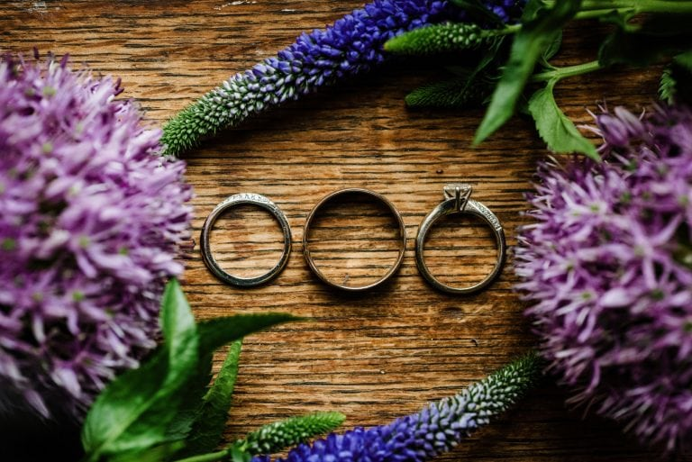 Wedding rings arrange on wooden table with flowers