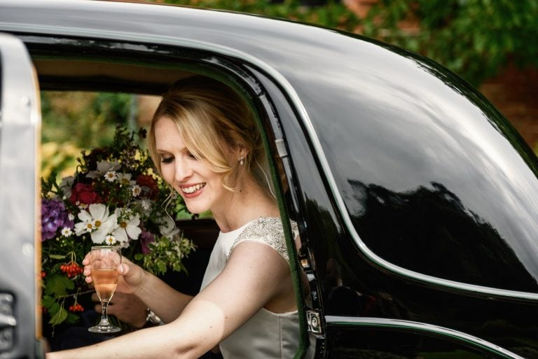 Bride happy as she exits wedding car with glass of champagne in her hand