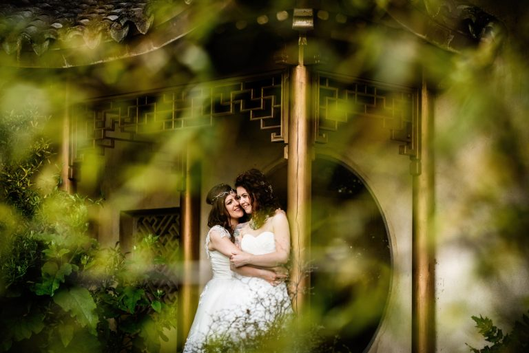 Two brides cuddled up in beautiful garden at Matara Centre in Gloucestershire