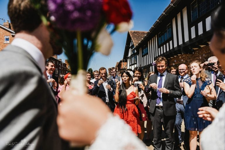 Wedding guests blow bubbles after ceremony at The Henley Room