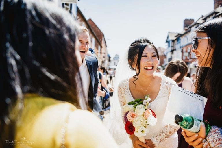 Bride laughing with friends after wedding ceremony