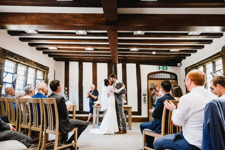 Bride and groom kiss during wedding ceremony at The Henley Room in Stratford