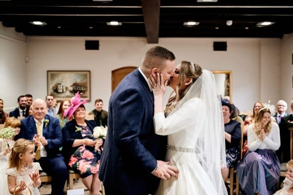 Bride and groom kiss during wedding at The Henley Room