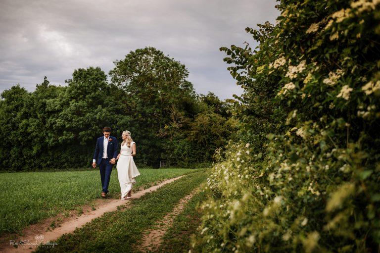 Bride and groom walking in field at village hall wedding