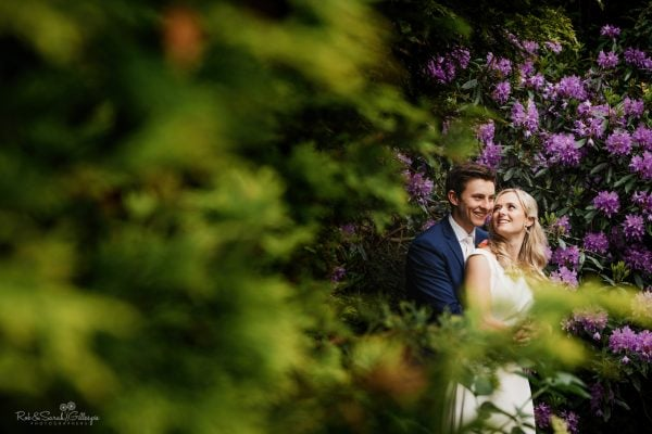 Bride and groom at village hall wedding amongst flowers