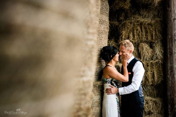 Bride and groom in hay barn at home wedding