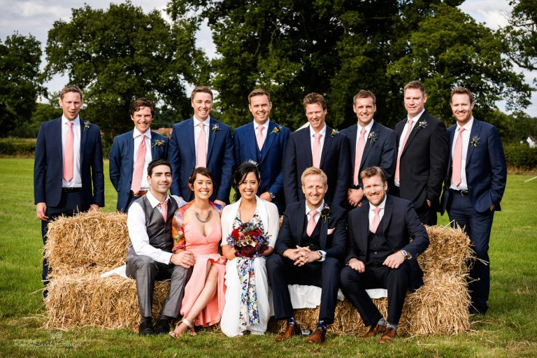 Home wedding group photo on bales of hay