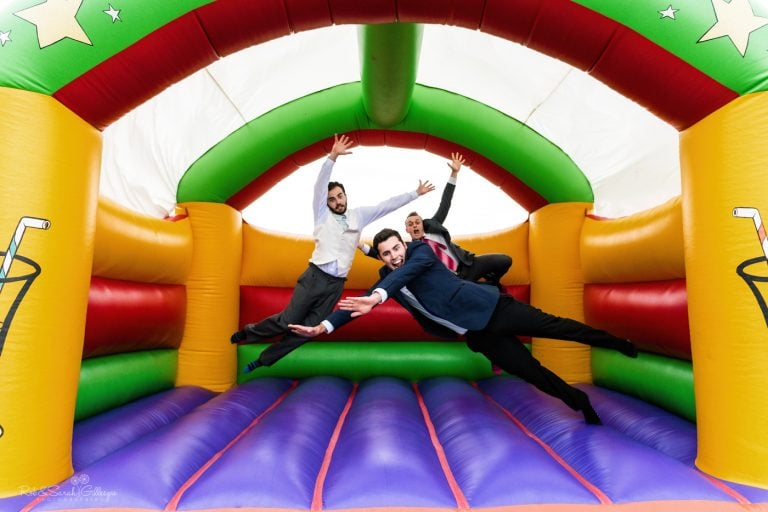 Wedding guests playing on bouncy castle at village hall wedding