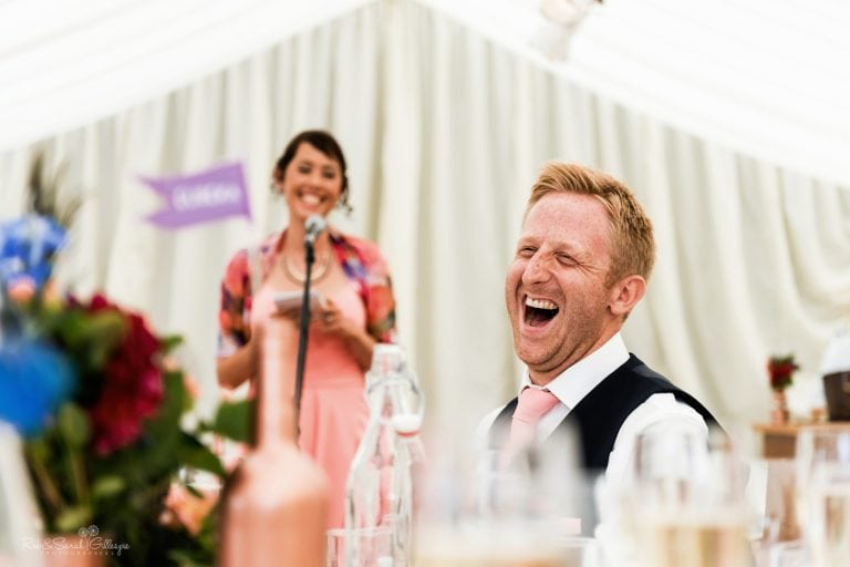 Groom laughing at speeches at home wedding