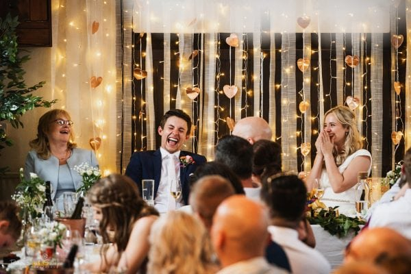 Bride and groom laughing at speeches in village hall wedding