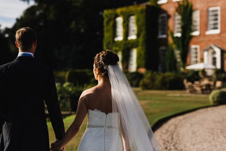 Bride and groom walking to Delbury Hall in Shropshire