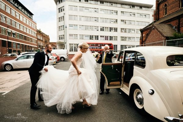 Bride and groom getting into old wedding car in Birmingham city centre