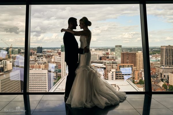 Bride and groom in front of large window looking out over Birmingham city centre