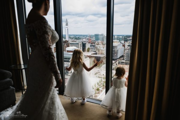 Bride and flowegirls looking out of window over view of Birmingham city centre