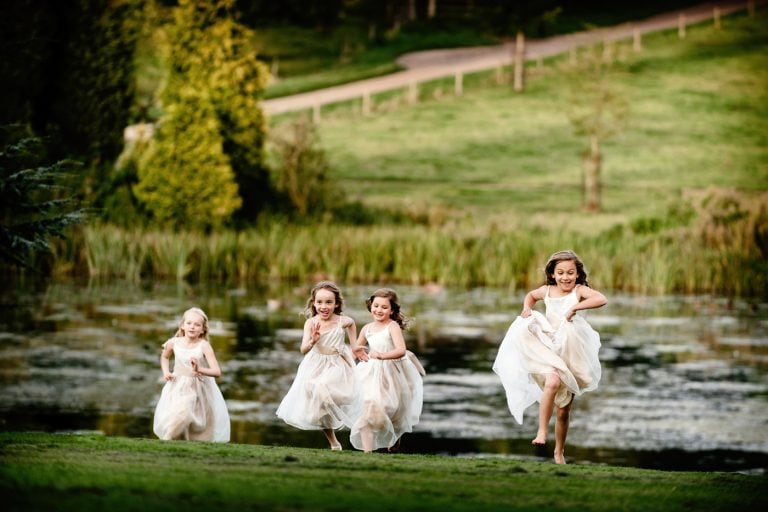 Flowergirls at wedding running across lawn