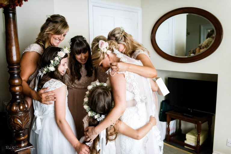 Bride and bridesmaids group hug before wedding
