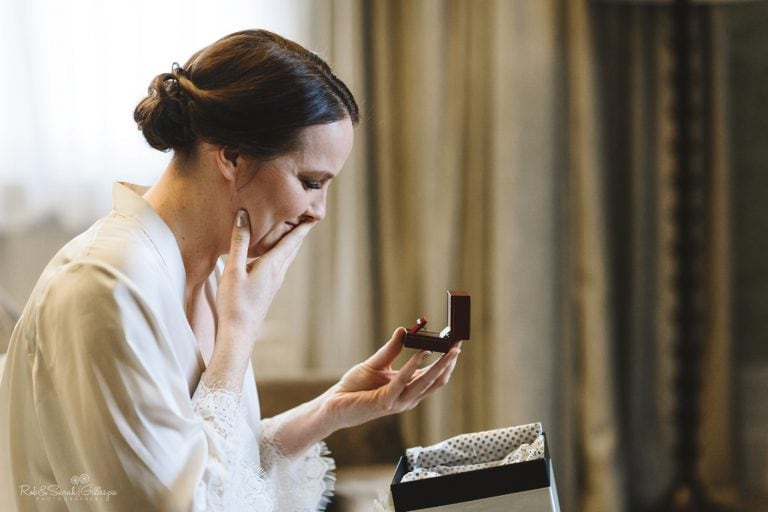 Bride reacting emotionally to gift from groom