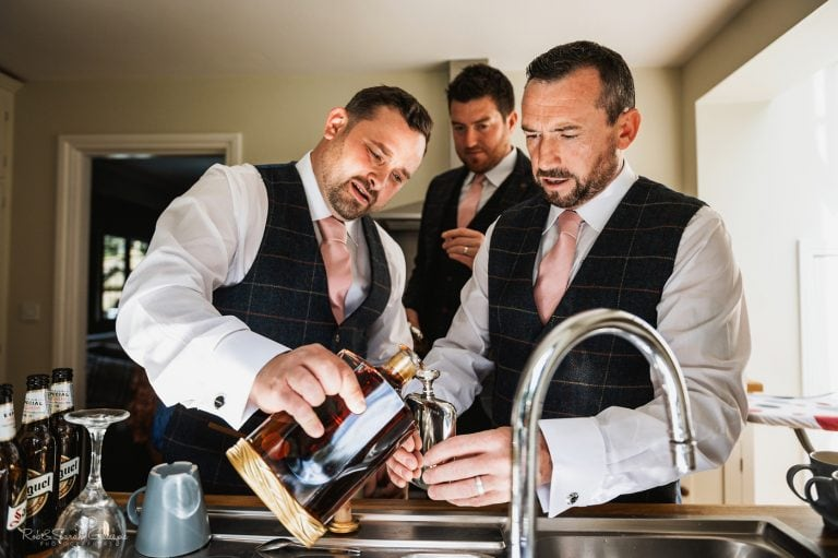 Groom and friends pour brandy into hipflask