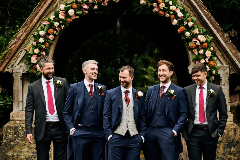 Group of groom and groomsmen laughing in front of church lychgate