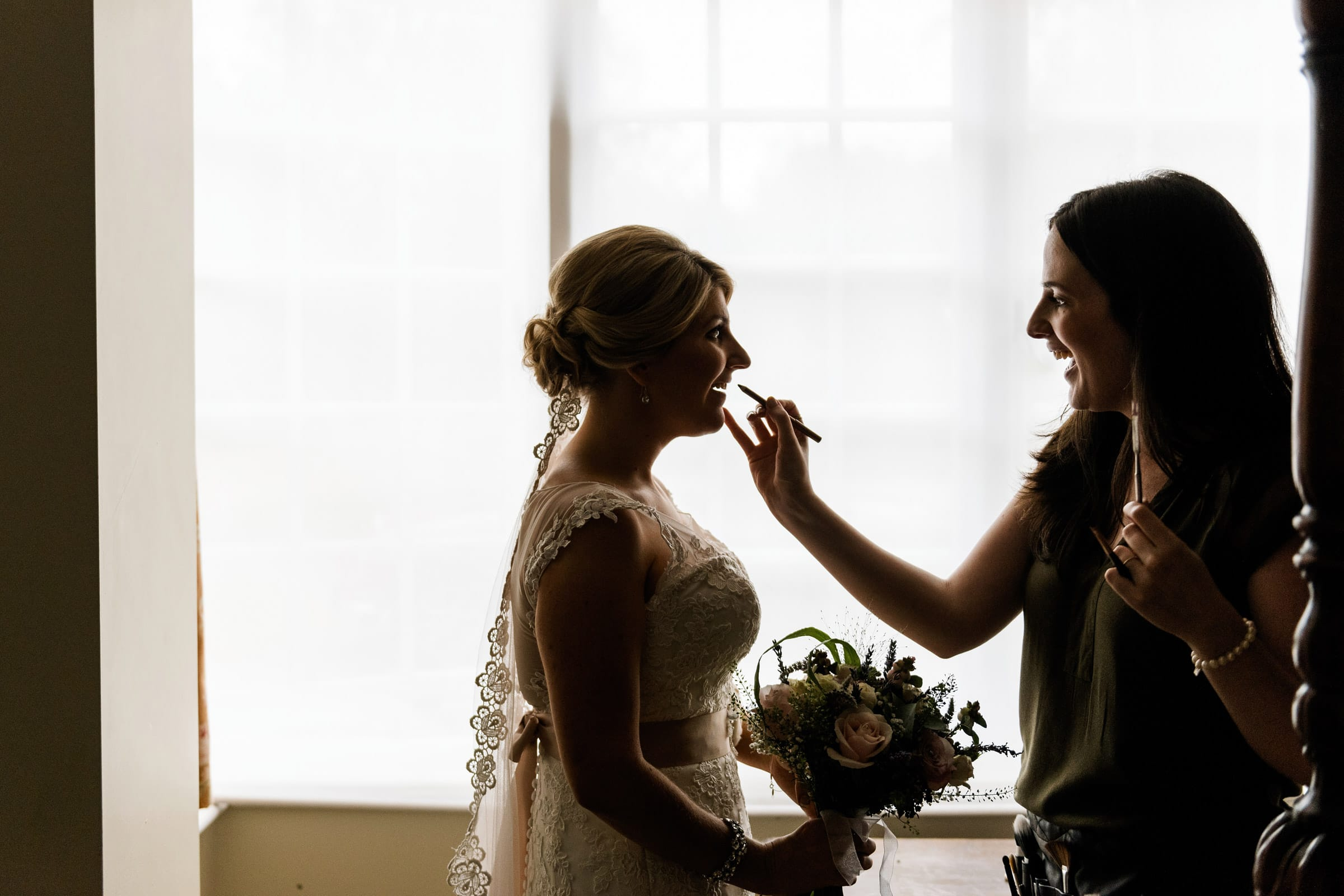 Bride has makeup applied silhouetted in window