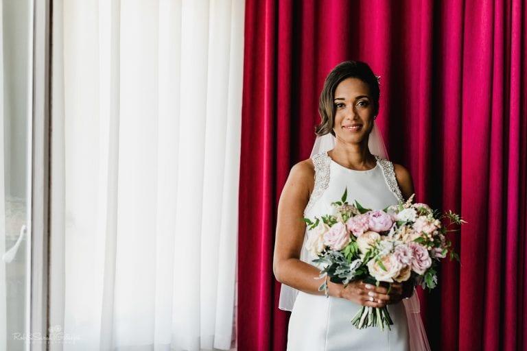 Portrait of beautiful bride with cerise curtain