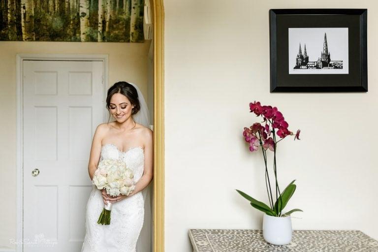 Portrait of bride in doorway with flowers