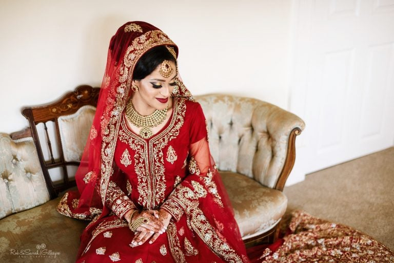 Portrait of bride in Indian wedding dress on sofa