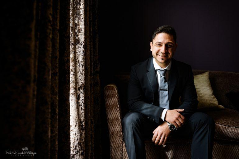 Portrait of groom sitting in window light in dark room