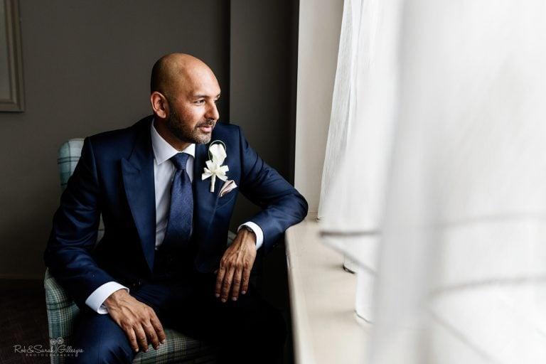 Portrait of groom sitting in window light