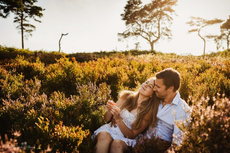 Engagement photo shoot with bride leaning into groom sitting in heather