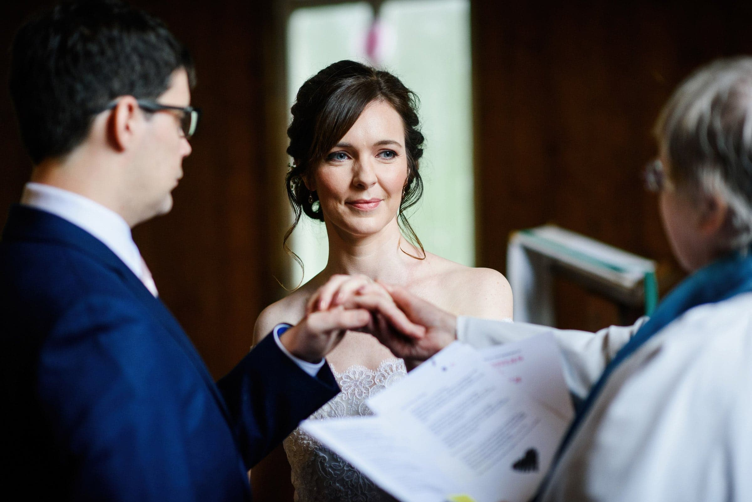 Bride and groom blessed by vicar during small wedding ceremony