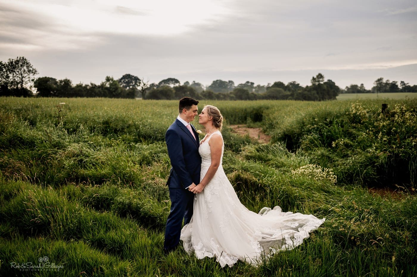 Bride and groom in lush green field