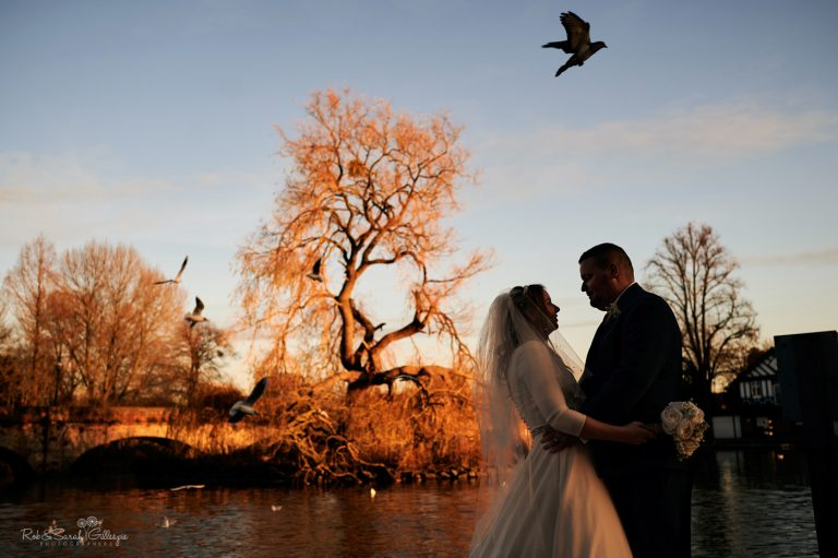 Bride and groom silhouetted against winter sky as birds fly past