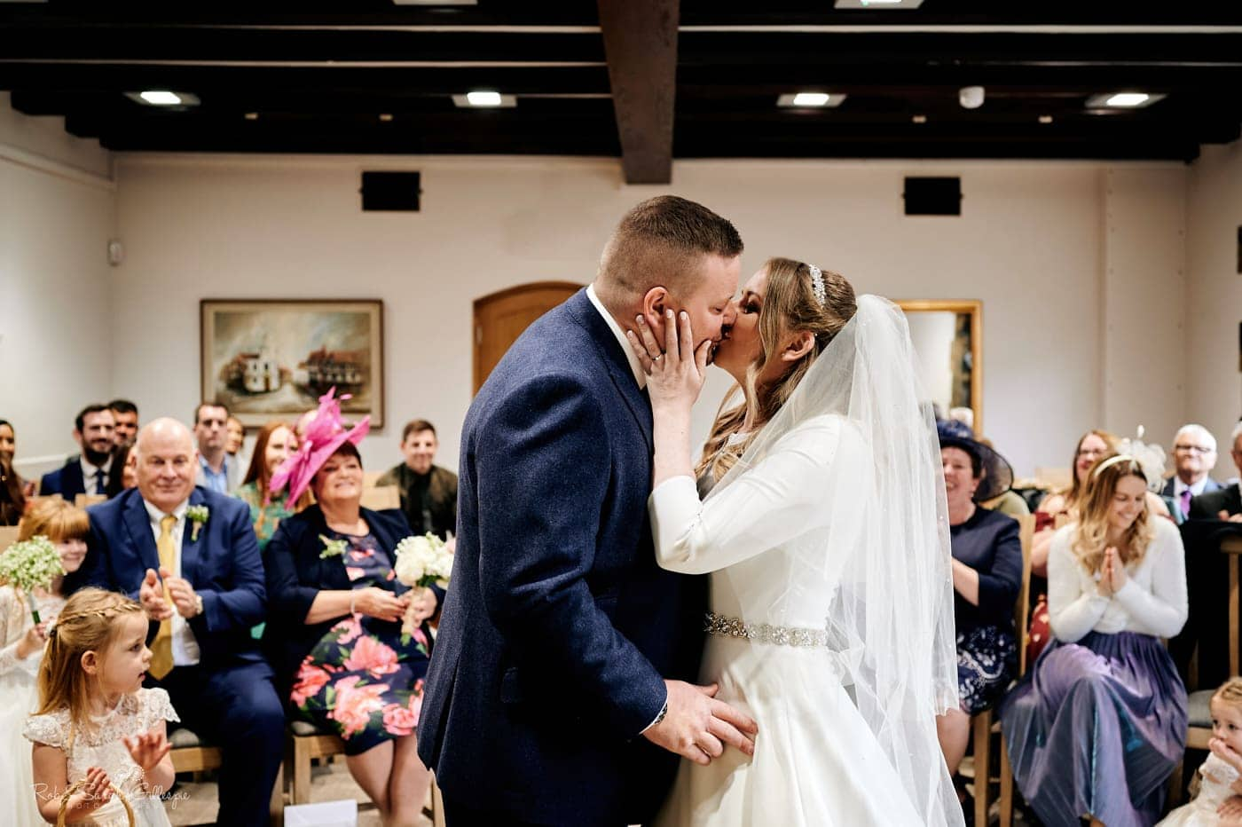 Bride and groom kiss during small wedding ceremony
