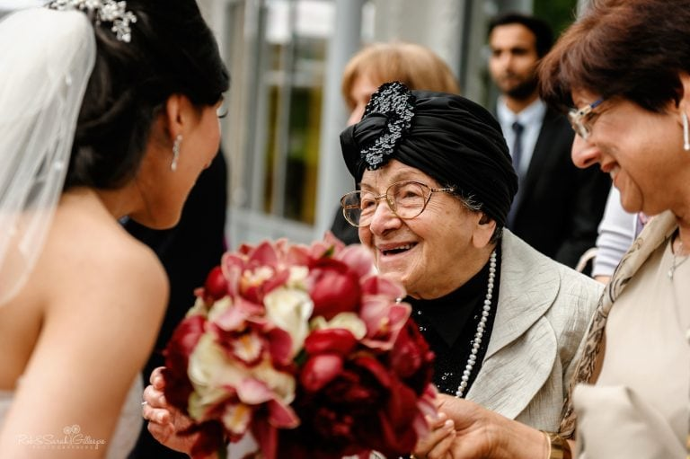 Elderly guest smiles with bride after small wedding ceremony