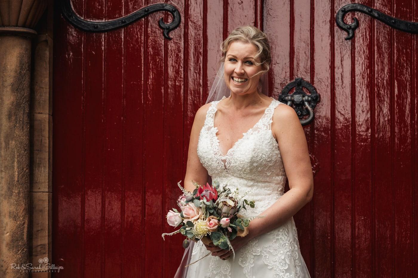Bride smiling in doorway of St John's church Walmley