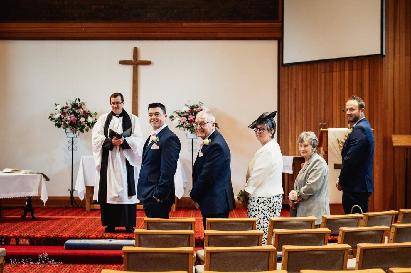 Groom and family turn to see bride entrance at small wedding ceremony