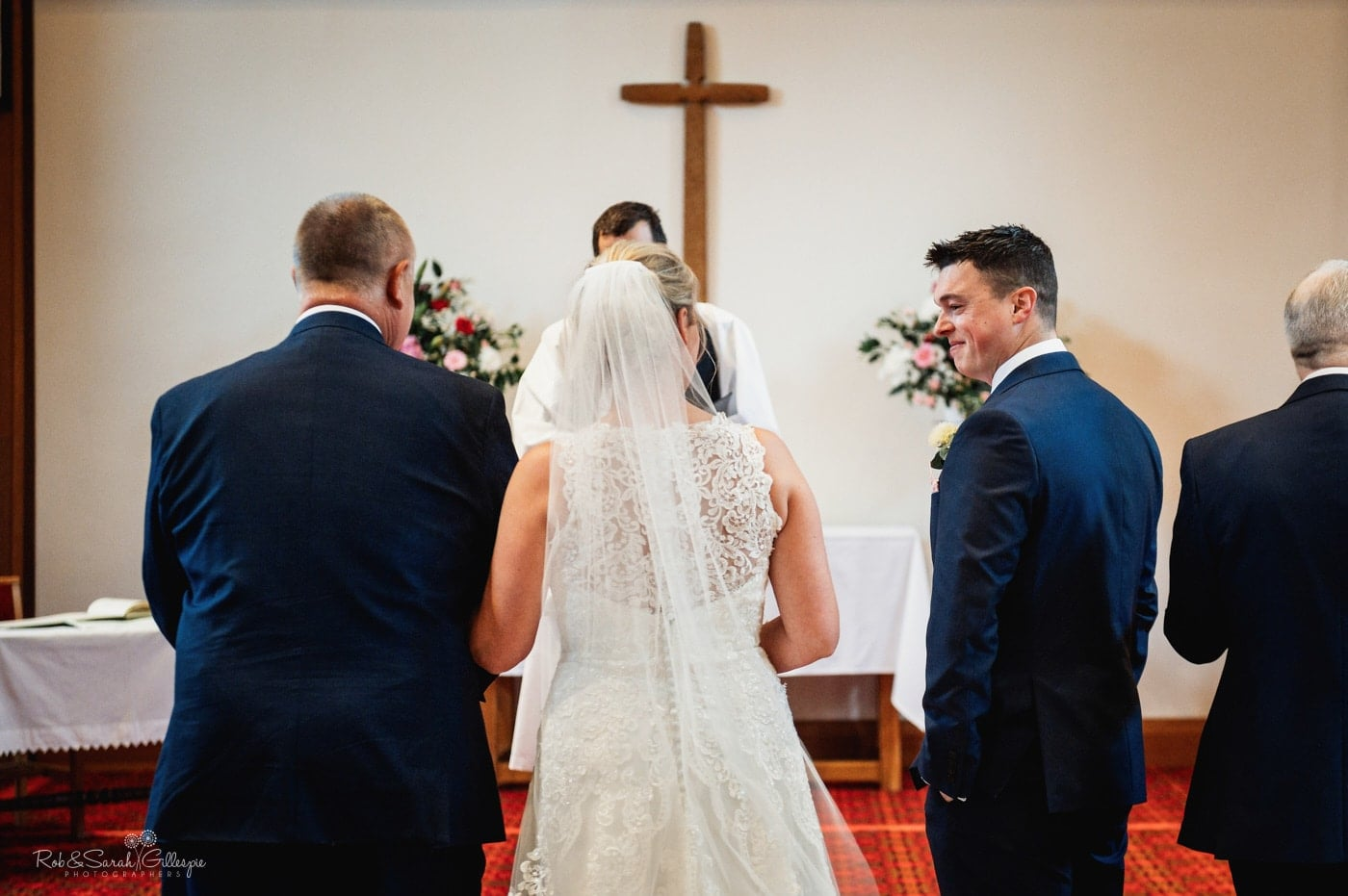 Groom smiling at bride as she walks up aisle for small wedding in chuch