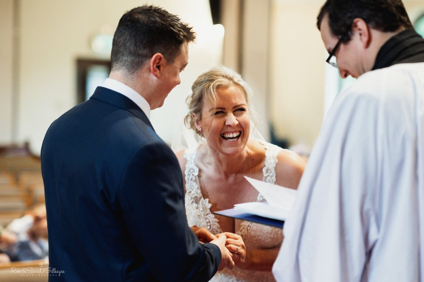 Bride laughing during small wedding ceremony in church
