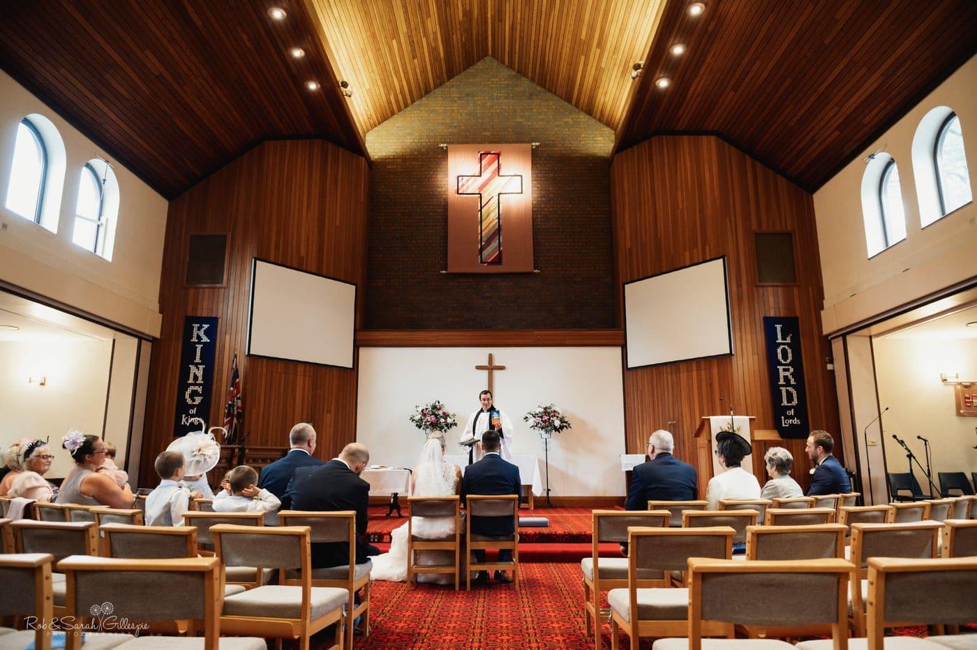 Vicars gives surmon during small wedding at St John's church Walmley