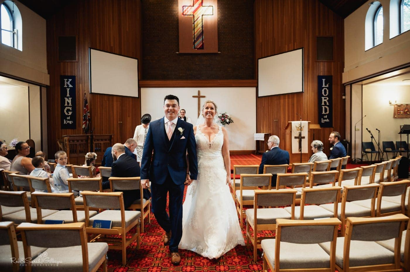 Bride and groom wak down aisle after small church wedding