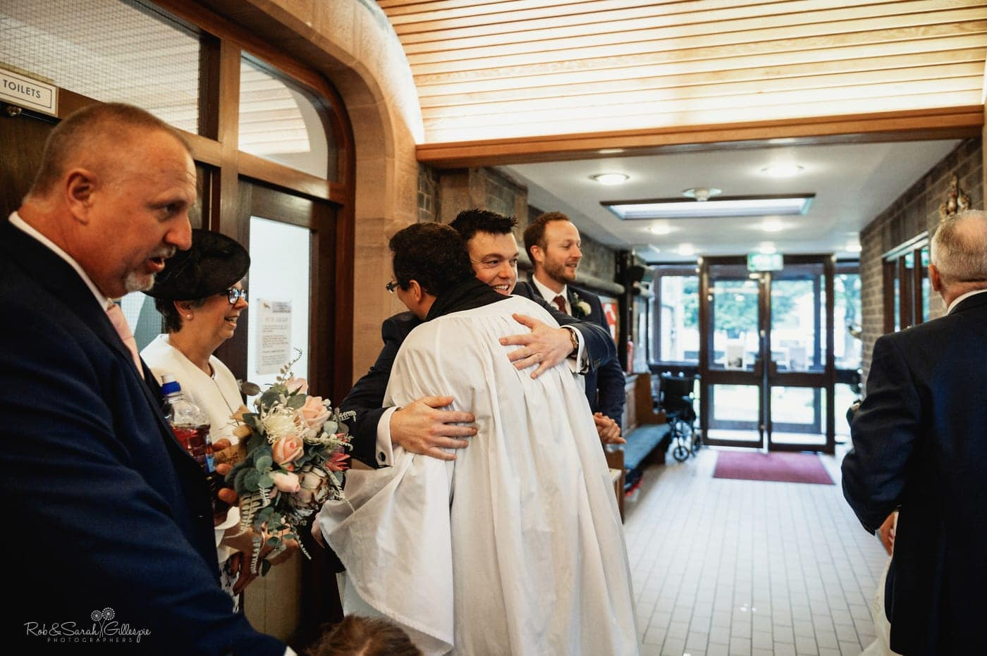 Groom hugs vicar afte small church wedding