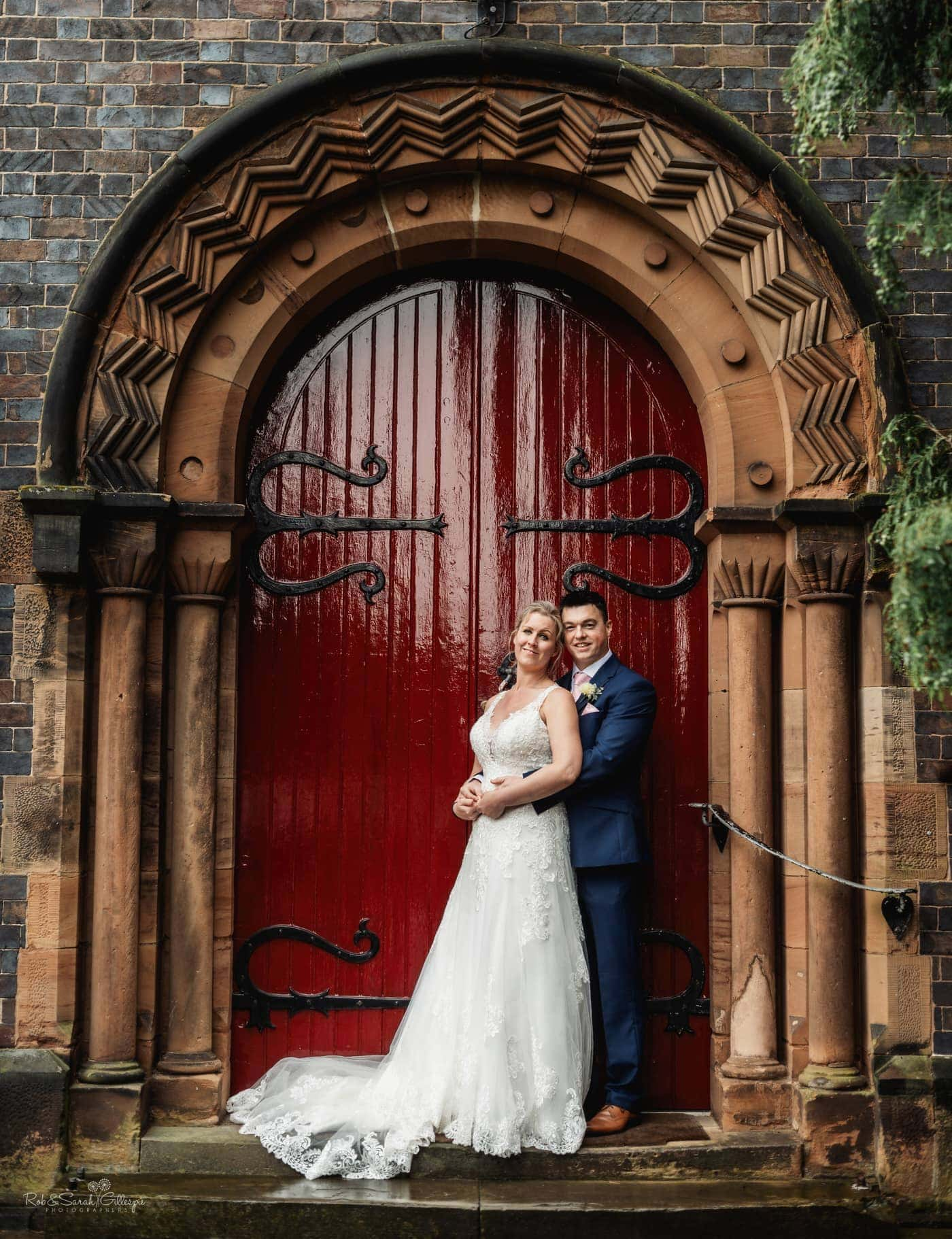 Bride and groom in beautiful doorway at St John's Church Walmley