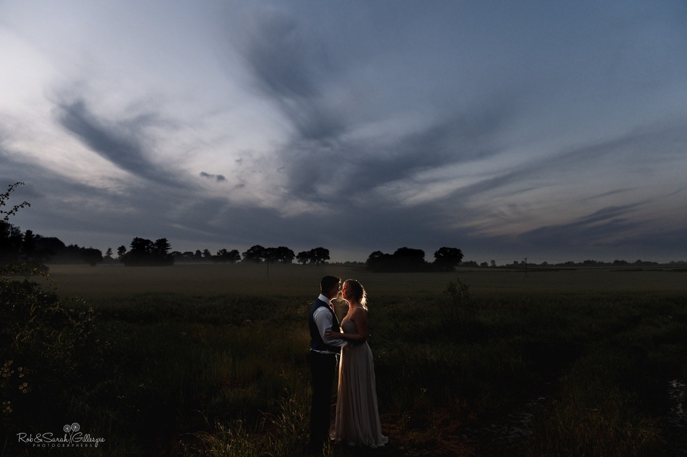 Bride and groom in field at Wishaw Country Sports during twilight