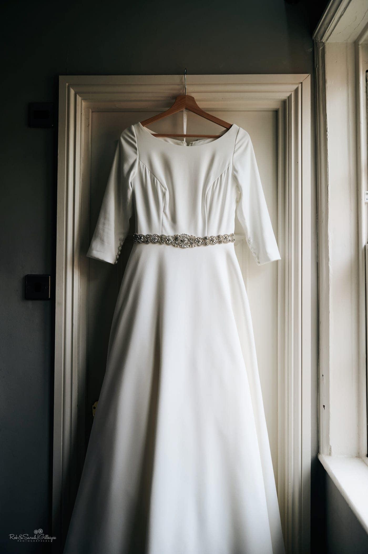 Wedding dress hanging up on doorframe in beautiful window light