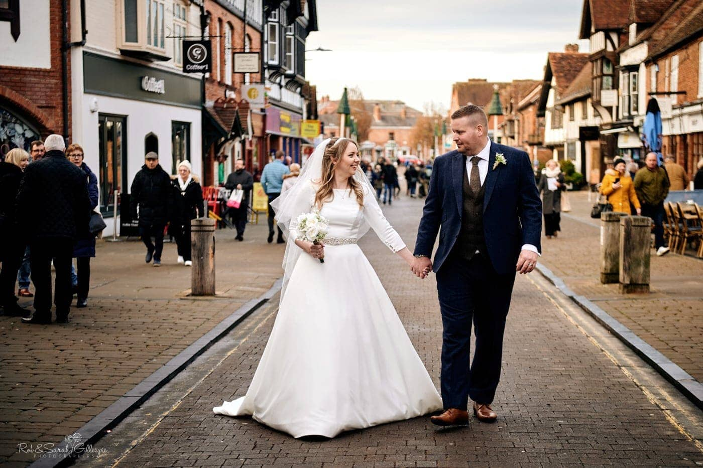 Bride and groom walk hand in hand through street in Stratford-upon-Avon